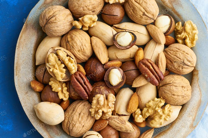 Classic blue in food. Mix of nuts on plate - walnut, almonds, pecans, macadamia