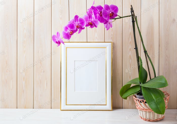 Gold decorated frame mockup with purple orchid in wicker basket