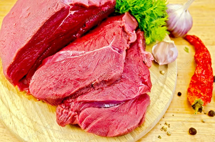 Meat beef on a wooden board with vegetables