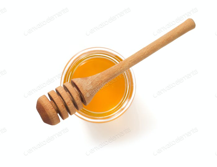 jar of honey and dipper on white background