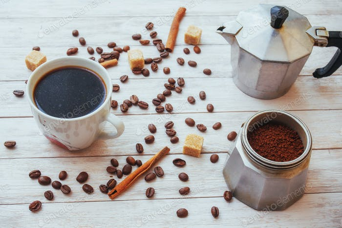 Kaffeebohnen und Tasse Kaffee auf dem Tisch auf dem Hintergrund