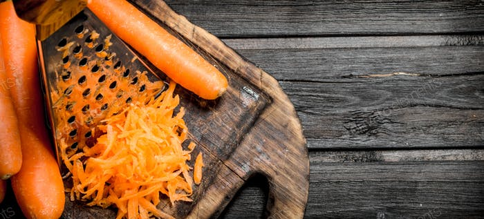 Grated carrots on a cutting Board with a grater.