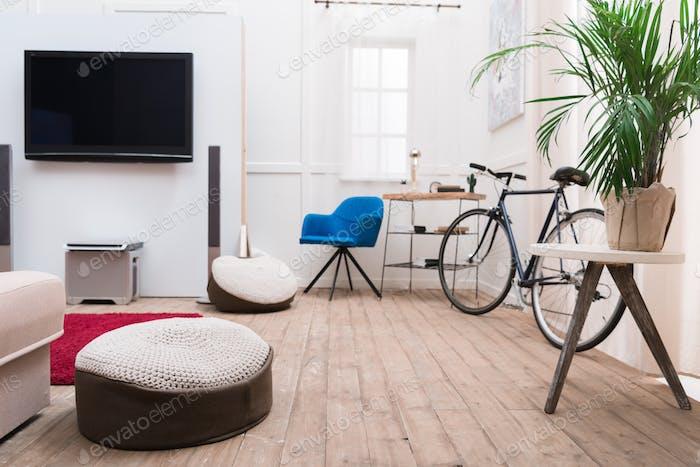 Интерьер гостиной с телевизором и велосипедом