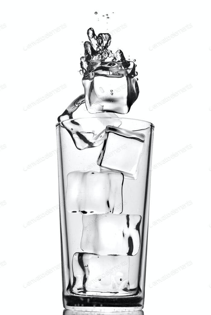 ice cubes dropped into glass with bubbles isolated on white