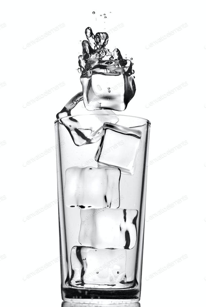 Eiswürfel in Glas mit Blasen auf weiß isoliert fallen