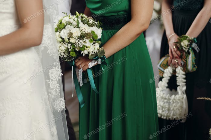 stylish bridesmaid standing holding wedding bouquet in old church at marriage ceremony