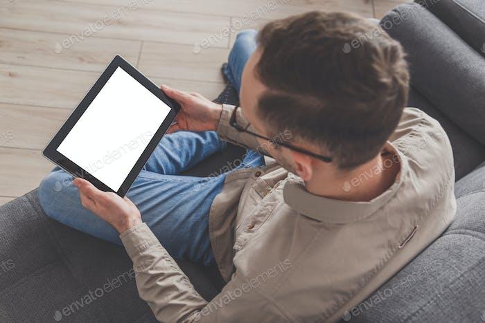 Surfen im Internet und Konferenzgespräche. Man benutzt einen Tablet-Computer, während man zu Hause auf einem Sofa sitzt
