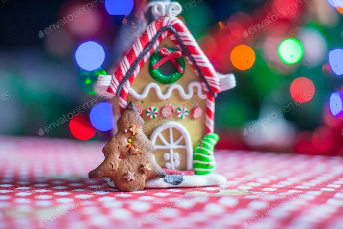 Gingerbread house decorated by sweet candies on a background of bright Christmas tree with garland