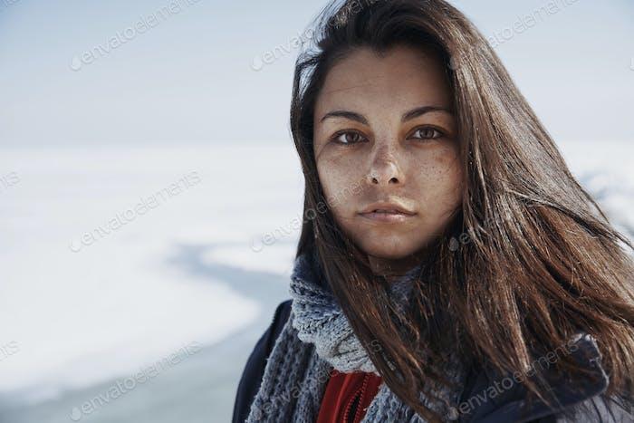 Junge erwachsene Frau draußen in eisiger Landschaft