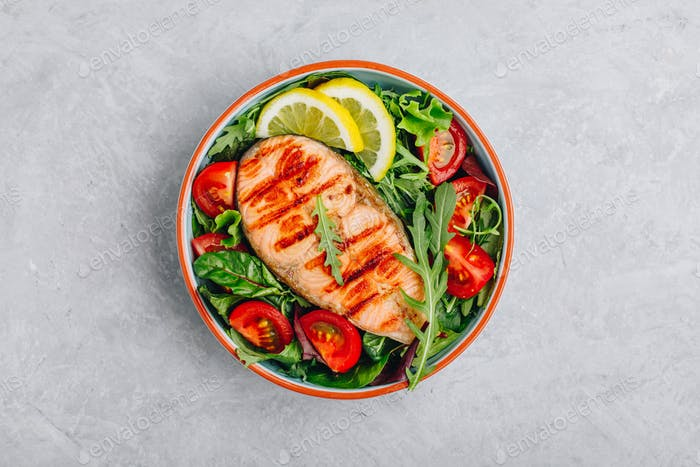 Grilled salmon steak with fresh green arugula salad and tomatoes