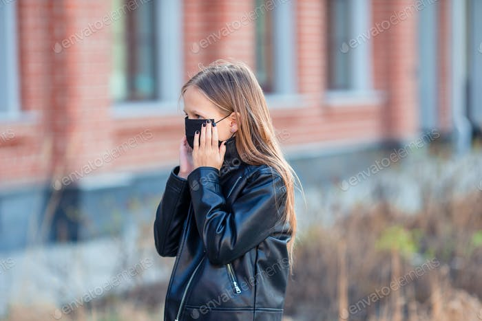 Girl wearing a mask on a background of a modern building