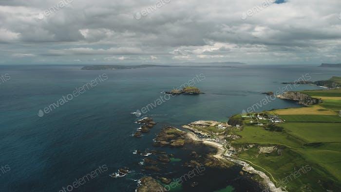 Klippe Luftlandschaft: felsiges Meeresufer. Irische Brennerei gegen die Natur: Wiesen und Wolken