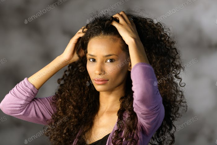 Cute attractive Afro American girl touching hair