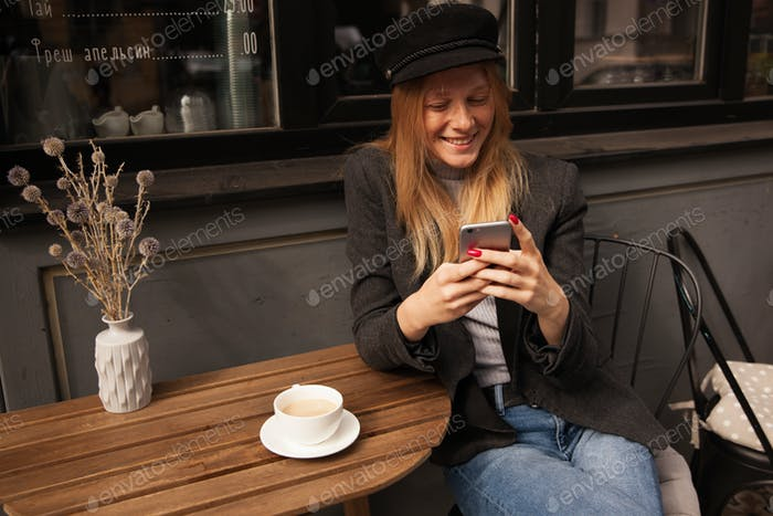 Beautiful young blonde lady with natural makeup having cup of coffee while waiting