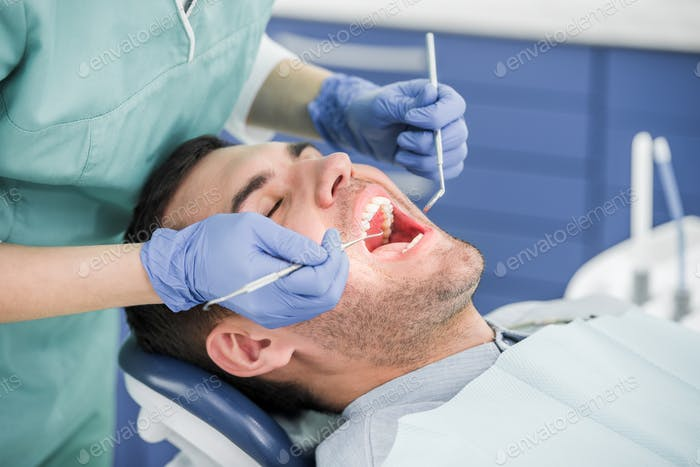cropped view of dentist in latex gloves examining patient with opened mouth