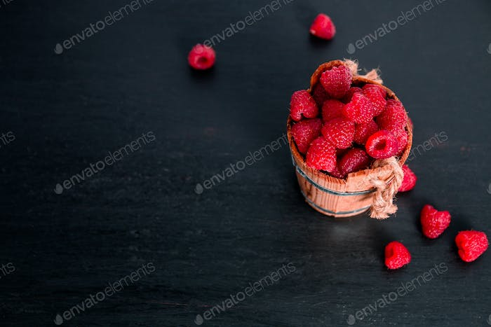 Red raspberries in a basket on black wooden background. Frame. Copy space. Top view.