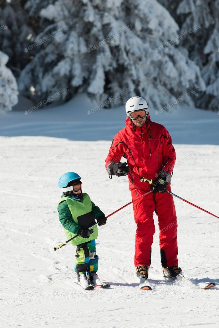 Ski instructor teaching little boy