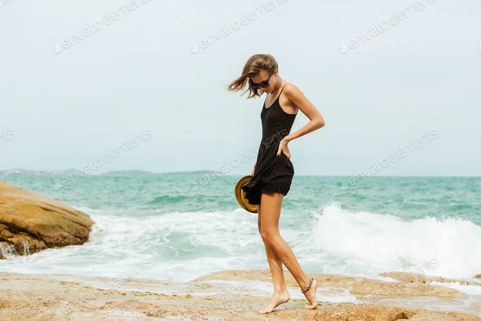 Cute girl in black summer dress at big stones.