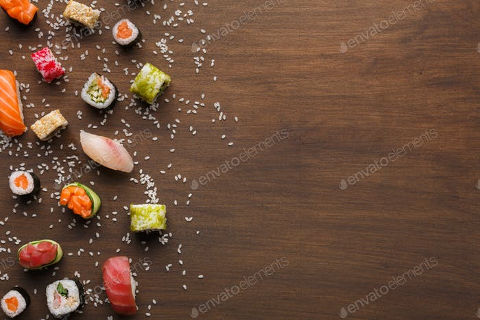 Set of sushi, maki and rolls with sesame on wooden rustic background, copy space