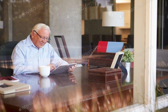 Senior Man Using Digital Tablet Through Window