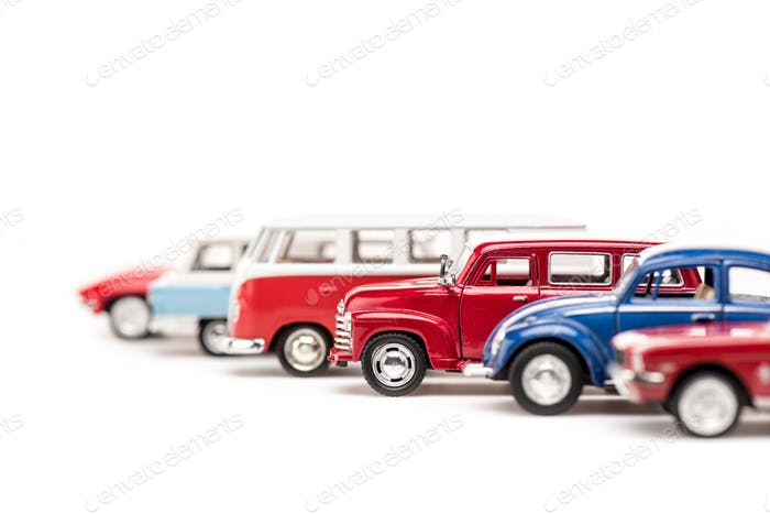 selective focus of colorful toy cars and bus on white