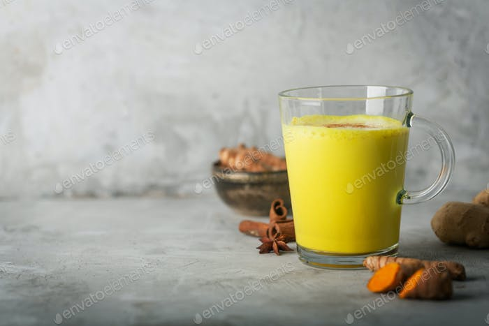 Golden Turmeric Milk On The Gray Background With Ingredients