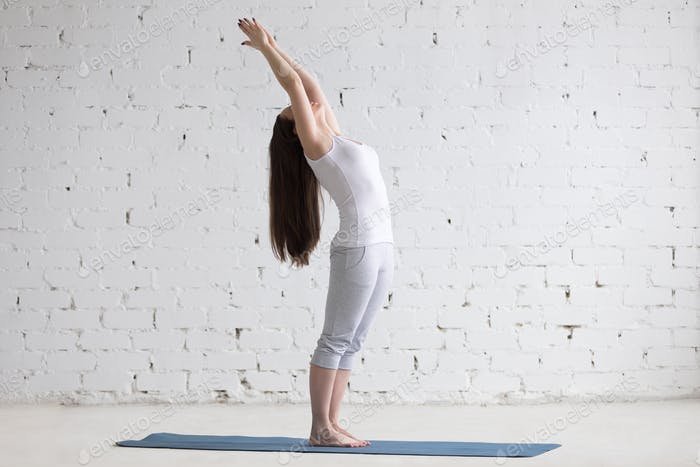 Beautiful sporty young woman doing standing backbend pose in whi