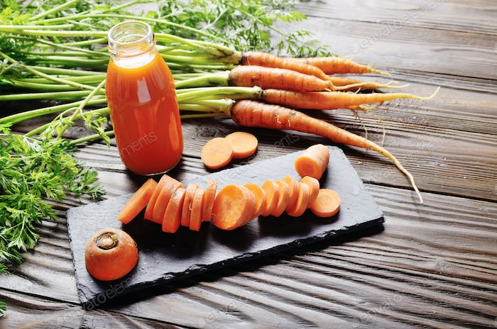 Closeup view at fresh organic vegetarian carrot juice in bottle on wooden kitchen table
