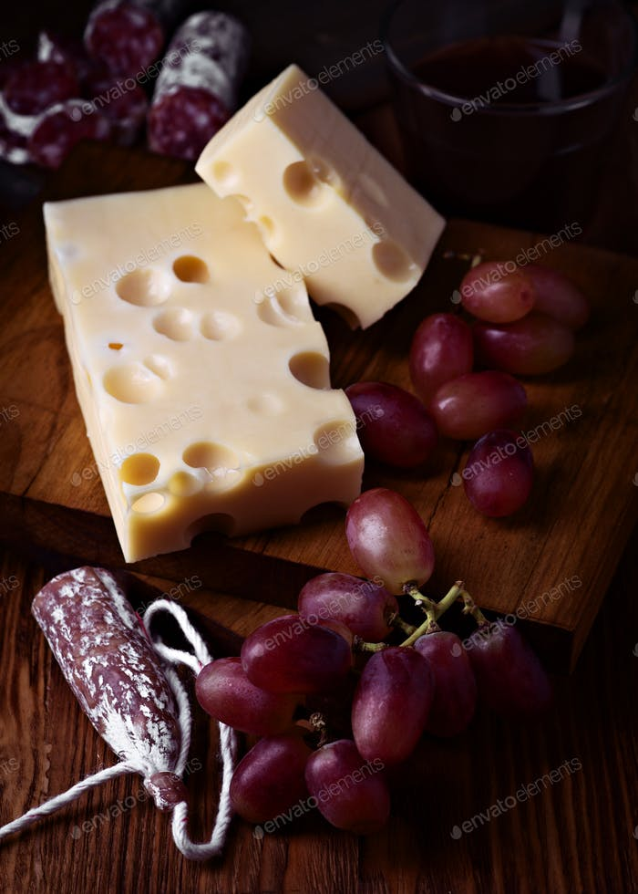 fuet spanish cheese and grape on wooden board