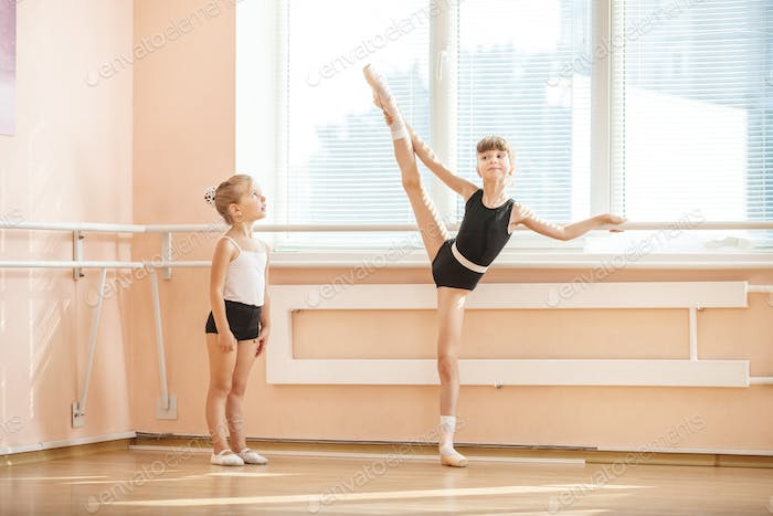 Little girl watching older ballet student practicing at barre
