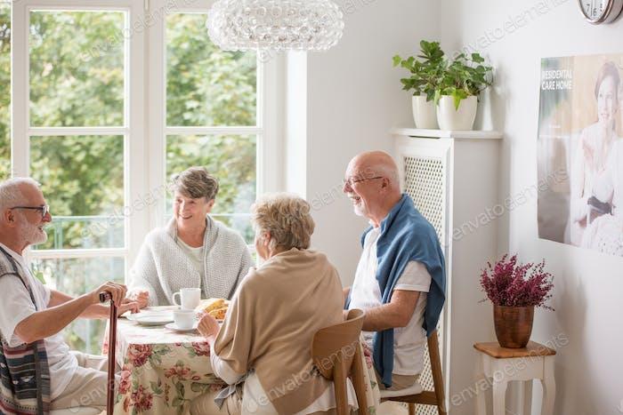 Group of senior friends sitting together at nursing home dining room