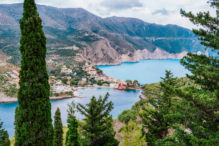 Frourio peninsular and Assos village with beautiful sea bay and cypress trees in foreground