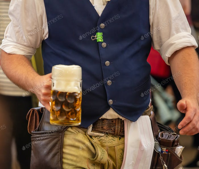 Oktoberfest, Munich, Germany. Waiter serving beer, closeup view