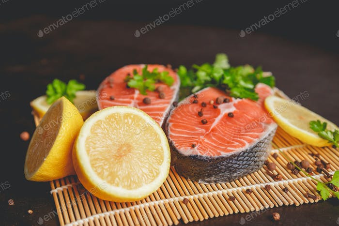 Salmon steaks with lemon and spices close up view.