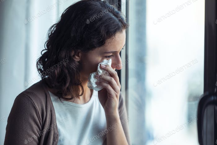 Sad young woman crying while looking through the window at home.