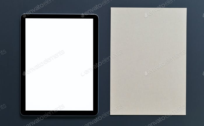 Tablet mockup blank screen and brown note pad on black background,Top view shot.