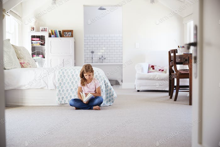 Young girl reading a book alone in her bedroom