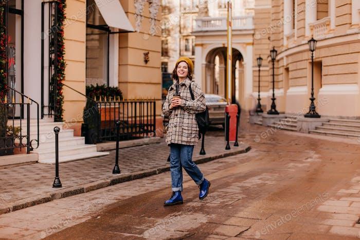 Full-length portrait of female student walking in city center. Girl in blue shoes Dr. Martins walks