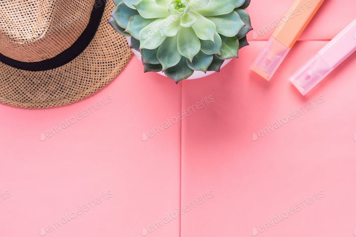 Coral pink flat lay with hat and markers