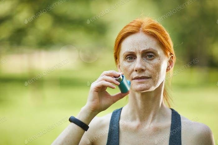 Freckled woman using inhaler