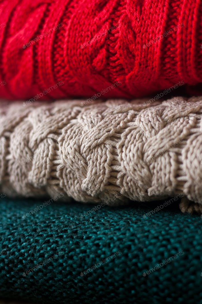 Stack of knitted sweaters close up. Beautiful cozy winter or autumn texture.