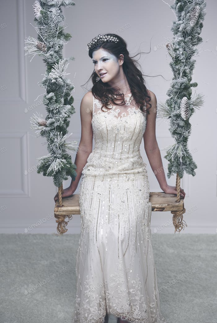 Serious snow queen or ice queen on swing