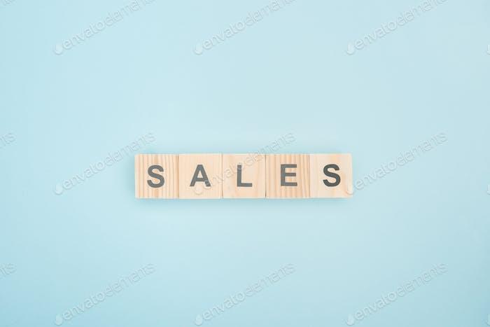 vista superior de las letras de ventas hechas de cubos de madera sobre fondo azul
