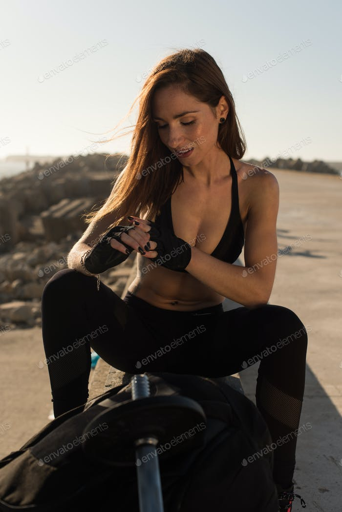 Fit woman after outdoor workout with weights