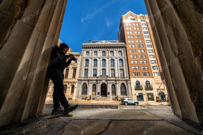 Asian young woman checking and using the camera over the bank of philadelphia,