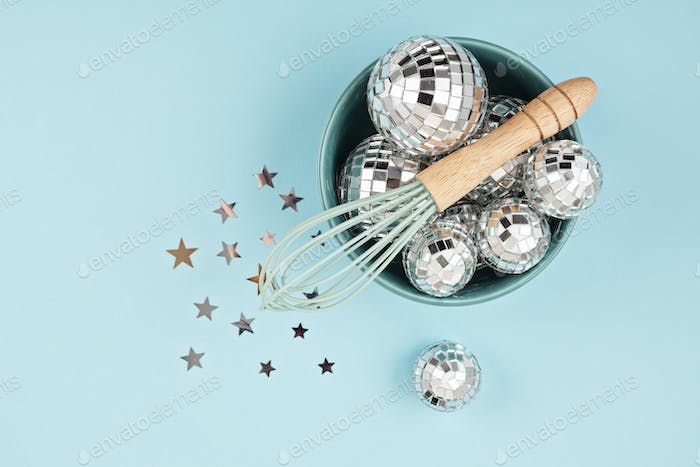 Flat lay with disco balls in the bowl with whisk. Party, fun, celebration planning