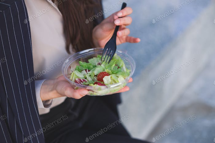 Office worker eats salad sitting outdoor
