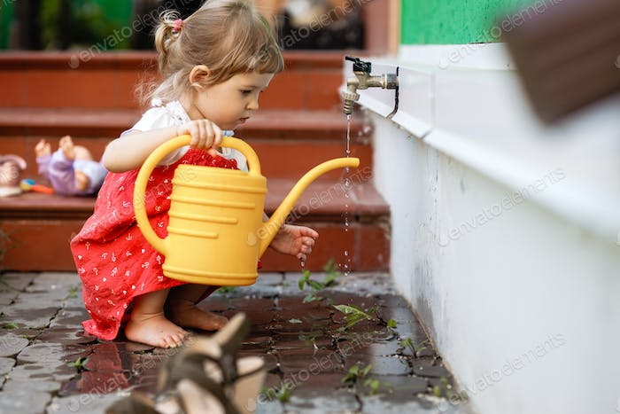 A little girl dressed in a sundress is drawing water in a watering can in the garden next to the