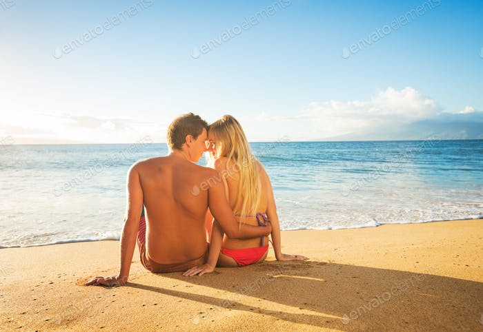 Paar beobachten den Sonnenuntergang auf tropischen Strand Urlaub