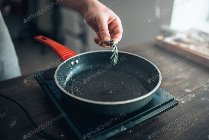 Male chef hands puts rosemary in a frying pan